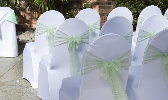 Rows of white chiars with a pale green bows tied on the backs